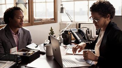 שני אנשים עובדים ליד שולחן, כאשר האישה משתמשת במחשב נישא פתוח