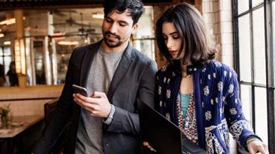שני אנשים במשרד מנהלים שיחת ועידה במכשיר נייד