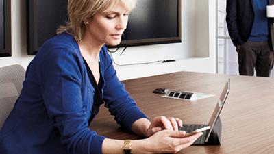 אישה עובדת בחדר ישיבות על מחשב נישא ומביטה בטלפון שלה