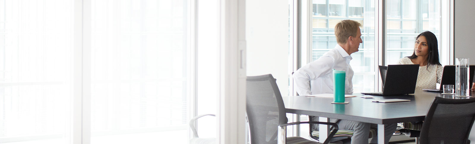 एक कॉन्फ़्रेंस कक्ष में लैपटॉप के साथ Office 365 Enterprise E3 का उपयोग कर रहे दो कर्मचारी.