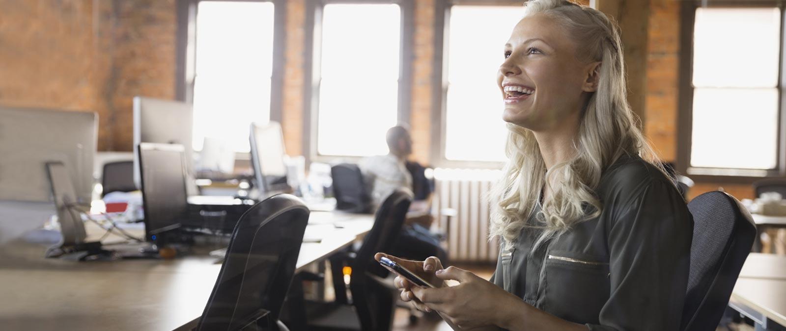 कार्यालय में एक महिला, स्मार्टफ़ोन पर Office 365 Business Essentials उपयोग कर रही है.