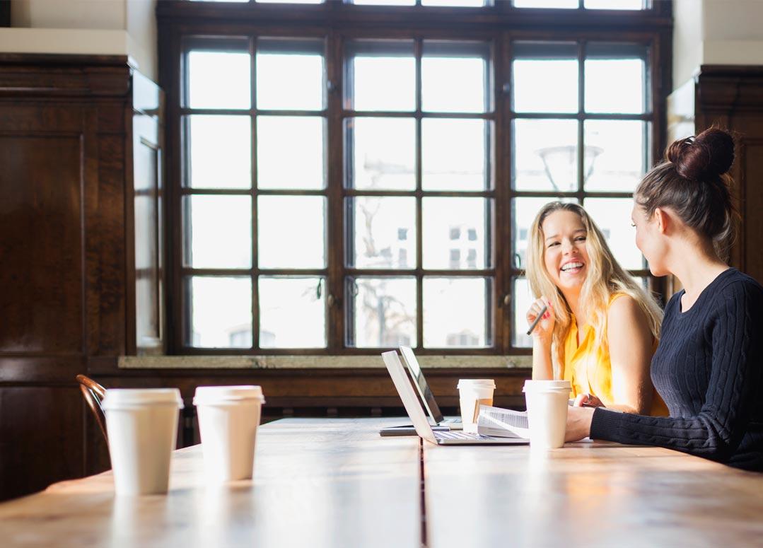 मेज के पास अगल-बगल बैठी दो महिलाएँ, अपने लैपटॉप पर Office 365 ProPlus उपयोग कर रही हैं.
