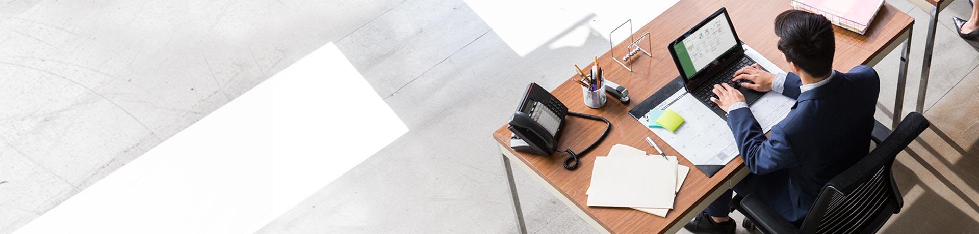 लैपटॉप पर Microsoft Project फ़ाइल पर कार्य करते हुए, कार्यालय में डेस्क पर बैठा हुआ व्यक्ति.
