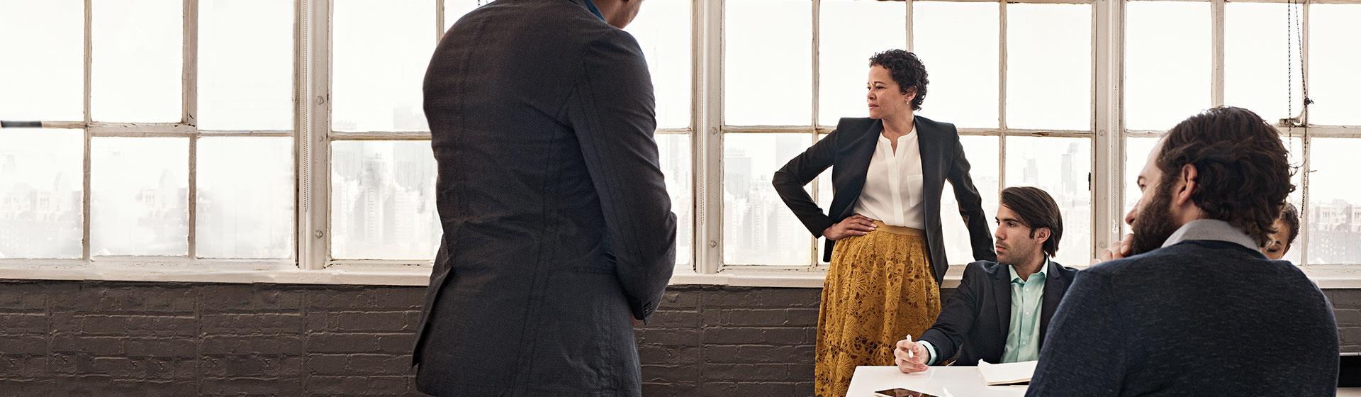 किसी कॉन्फ़्रेंस कक्ष में किसी मेज़ पर साथ में बैठा और खड़ा हुआ सहकर्मियों का समूह