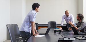 कॉन्फ़्रेंस रूम में अपने लैपटॉप पर Office 365 Enterprise E3 का उपयोग करते हुए तीन आदमी.