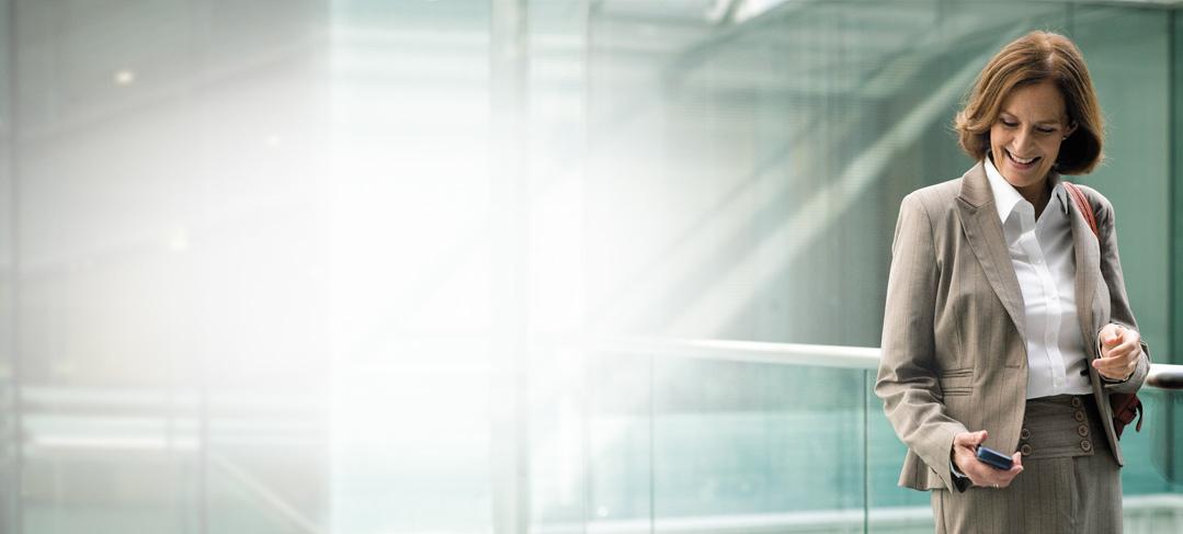 Poslovna žena ustaje dok na mobitelu koristi Exchange Online arhiviranje.