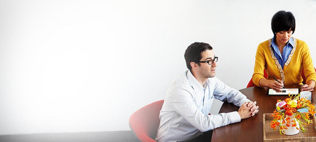 Tri osobe tijekom sastanka za stolom koriste Office 365 Nonprofit na tabletima i telefonima.