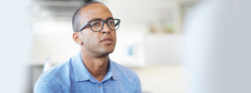 Muškarac sjedi u uredu, pročitajte iskustva korisnika o načinu na koji tvrtke i ustanove koriste Project.