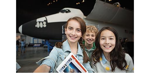 Troje djece smiješi se ispred zrakoplova. Informirajte se o suradnji s drugima u sustavu Office