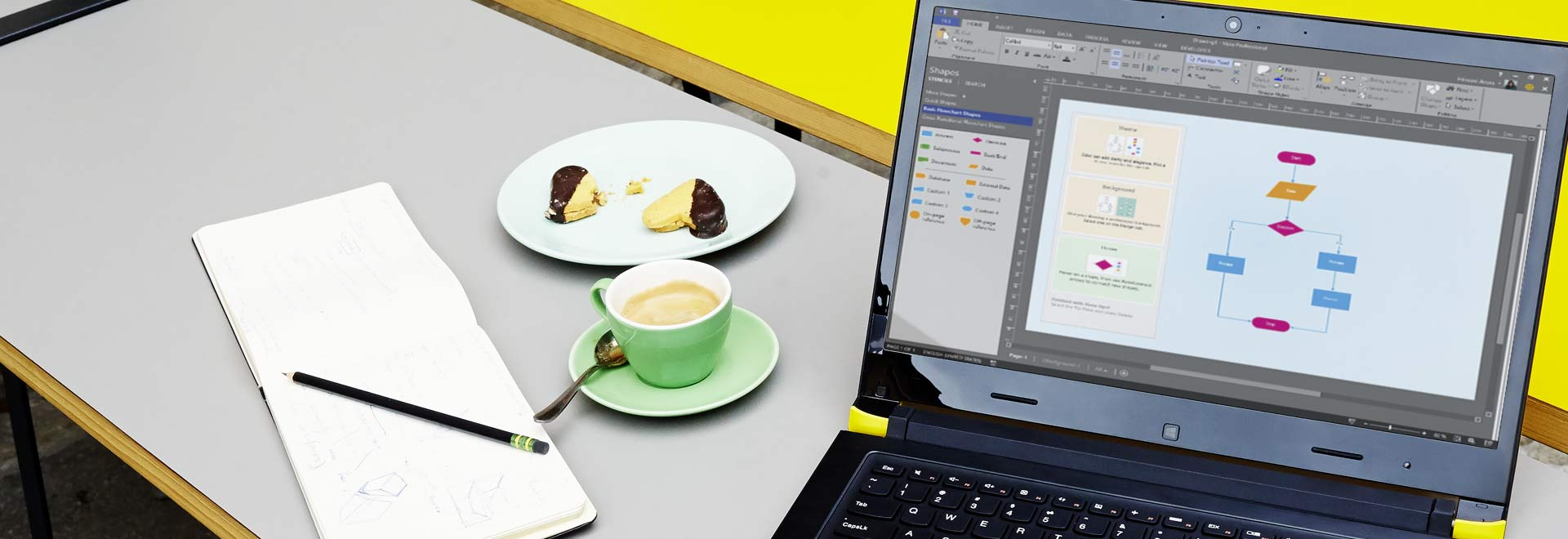 Close-up of a laptop on a table, showing a Visio diagram with editing ribbon and pane