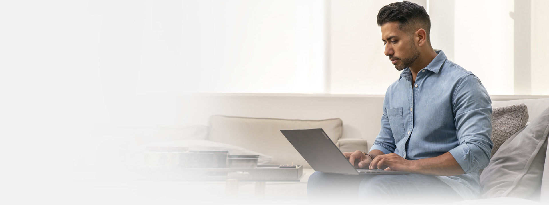 Kanapén ülő, laptopot használó férfi