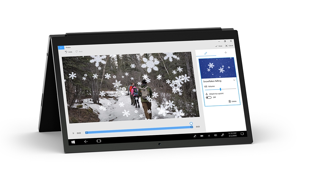 Laptop sátor módban a Fényképek alkalmazással, amelyben túrázók képe látható úgy, hogy az erdő 3D hópelyhekkel van díszítve.