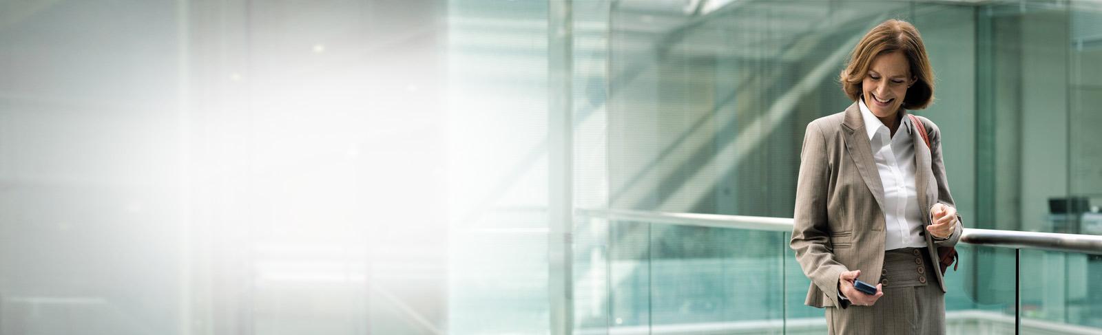 Egy üzletasszony állva használja az Exchange Online Archiválást a telefonján.