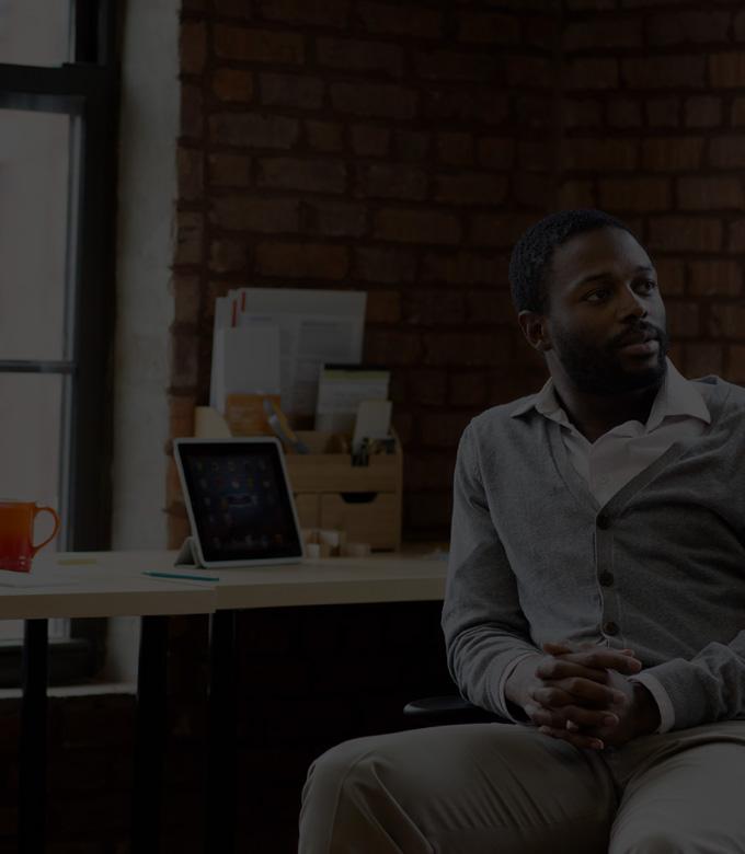 Egy íróasztalnál ülő, az Office 365 Vállalati Prémium verziót használó férfi, táblagéppel és laptoppal.
