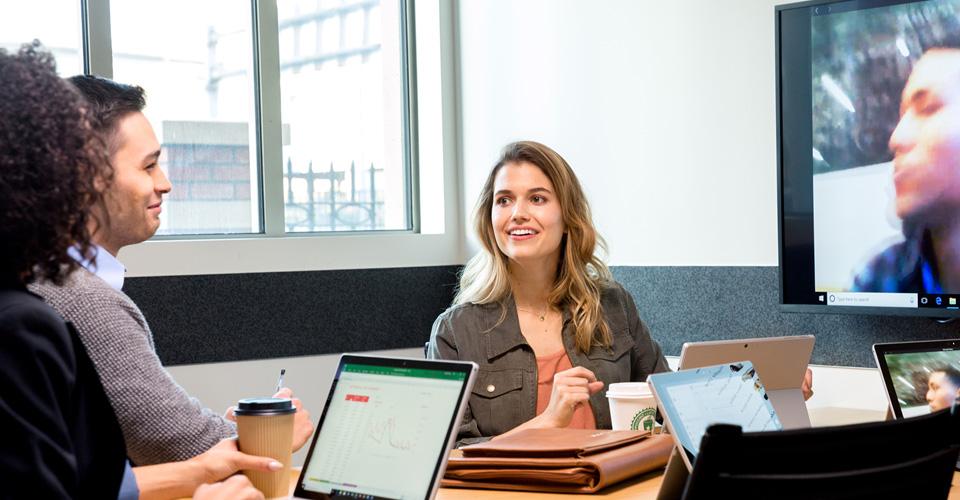 Munkatársakból álló csoport videohívás közben egy konferenciateremben