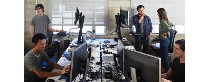 Öt személy számítógépen dolgozik vagy beszélget egy közös munkakörnyezetben.