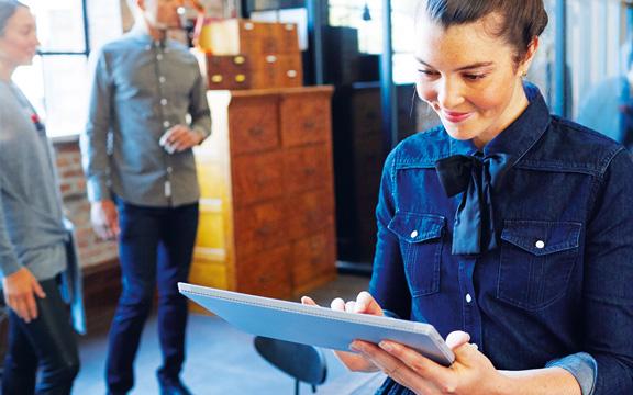 Egy álló nő, amint a Delve-et használja egy Surface készüléken.