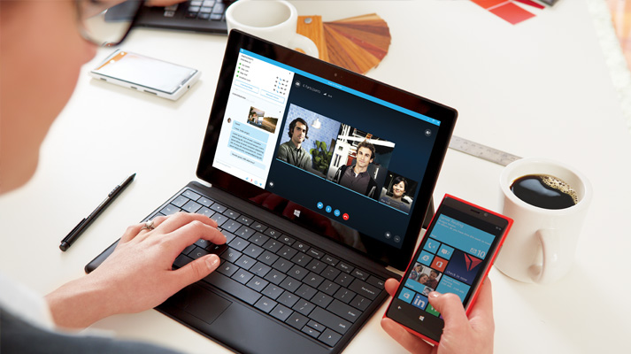 Egy nő táblagépen és telefonon Office 365-öt használva dolgozik közösen a dokumentumokon