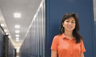 Egy nő egy adatközpontban. A SharePoint Online nagyvállalati szintű megbízhatóságot nyújt.
