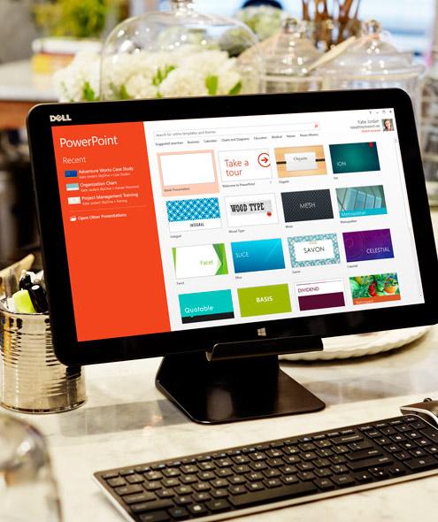 Monitor PC menampilkan galeri desain slide PowerPoint.