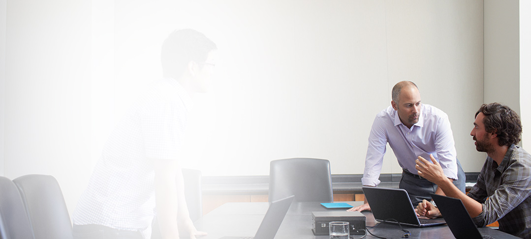 Tiga pria dengan laptop rapat di ruang konferensi menggunakan Office 365 Enterprise E4.