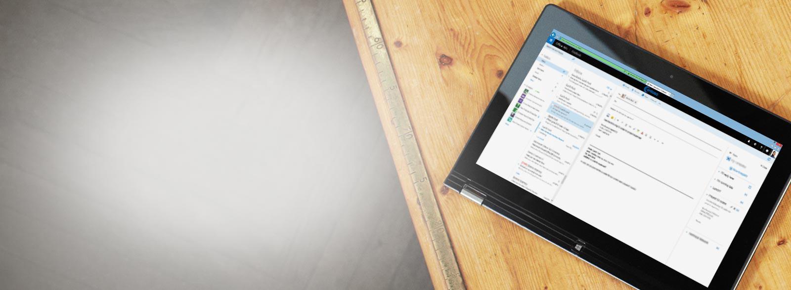Tablet di meja, memperlohatkan close-up kotak masuk email bisnis, didukung oleh Exchange.