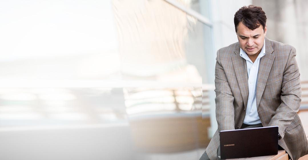 Seorang pria sedang bekerja dengan laptopnya, menggunakan email bisnisnya yang didukung oleh Exchange Online.
