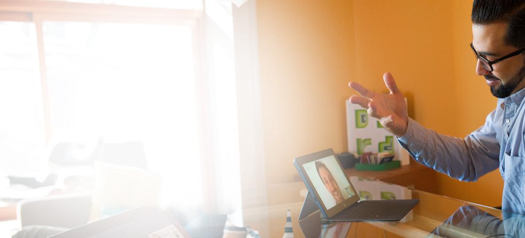 Seorang pria di konferensi video meja pada sebuah tablet menggunakan Office 365.