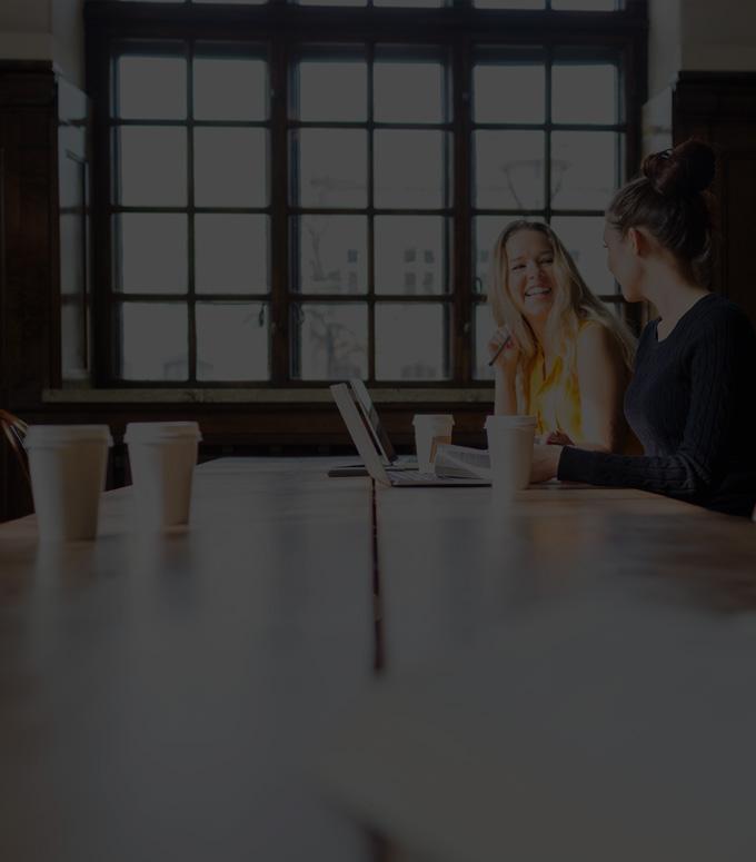 Dua wanita duduk bersebelahan di meja yang sama, menggunakan Office 365 ProPlus di laptop mereka.