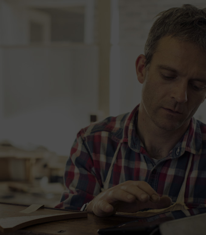 Pria di sebuah bengkel menggunakan Office 365 Bisnis pada tablet.