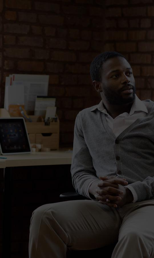 Pria duduk di belakang meja dengan tablet dan laptop, menggunakan Office 365 Bisnis Premium.