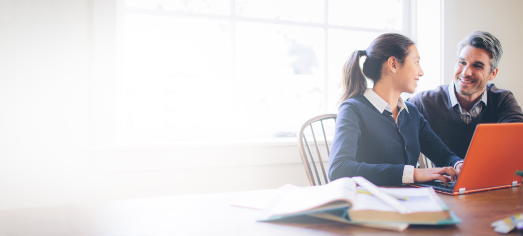 Seorang guru membantu siswa yang sedang mengetik pada laptop di meja.