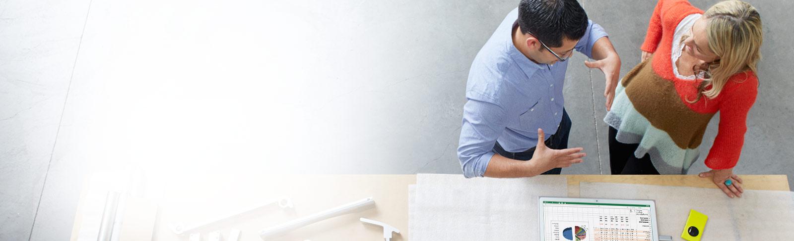 Seorang pria dan wanita berdiri di depan meja gambar menggunakan Office 365 ProPlus di tablet.