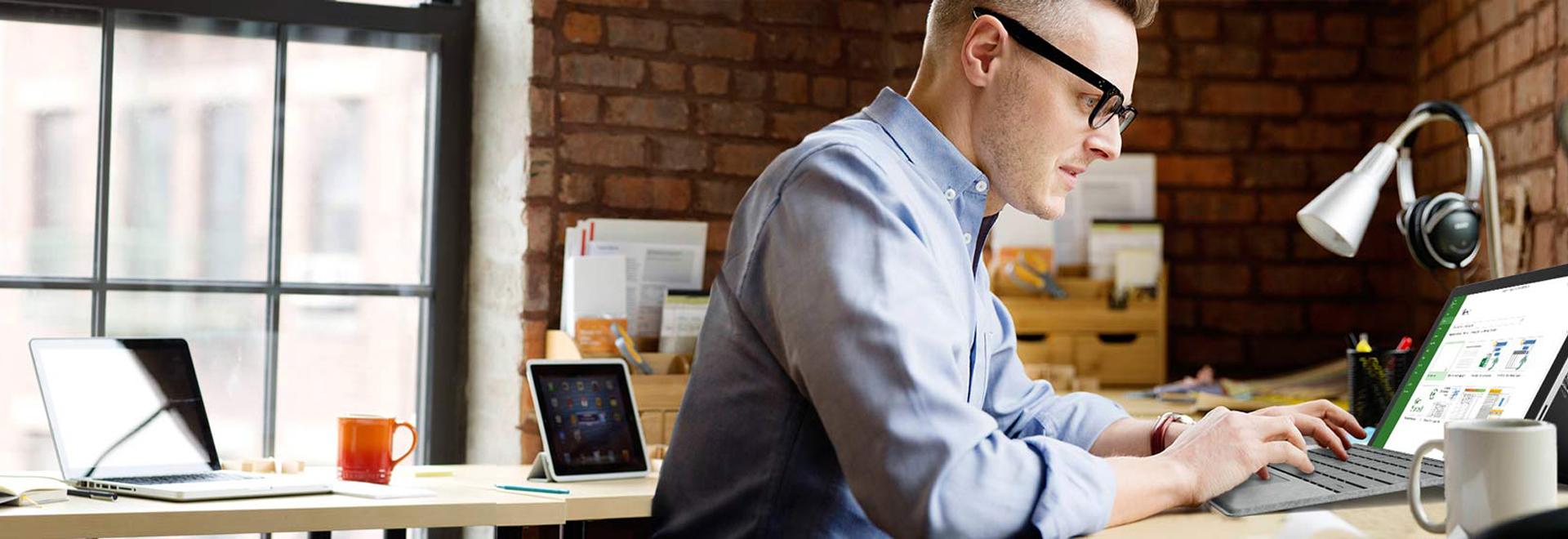 Seorang pria duduk di depan meja dan bekerja pada tablet Surface, menggunakan Microsoft Project.