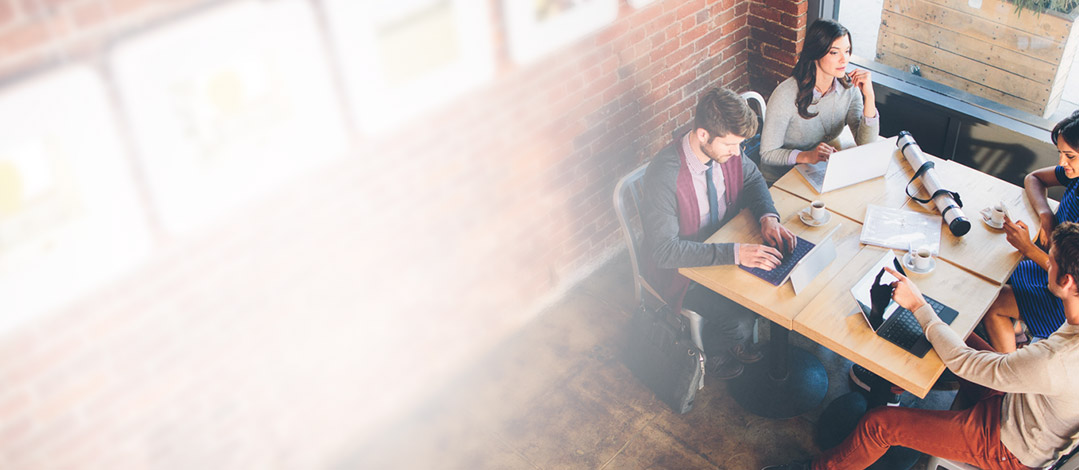 Dua orang pria dan dua orang perempuan di meja kafe, menggunakan Yammer di tablet dan minum kopi.