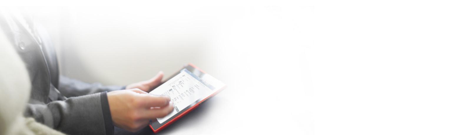 Close-up seseorang sedang duduk, bekerja di tablet yang sedang dipegang di tangan kirinya.