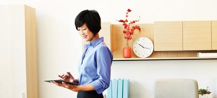Seorang perempuan sedang bekerja di kantor dengan tablet, menggunakan Office Professional Plus 2013