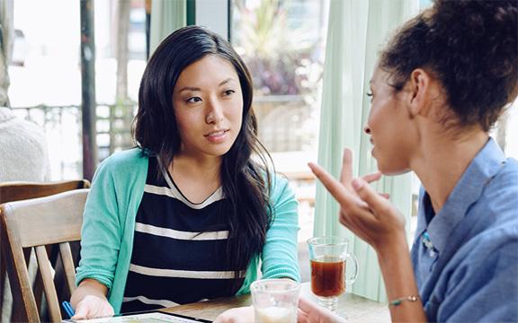 Dua wanita sedang bekerja di sebuah meja, menggunakan tablet dengan Office Delve.