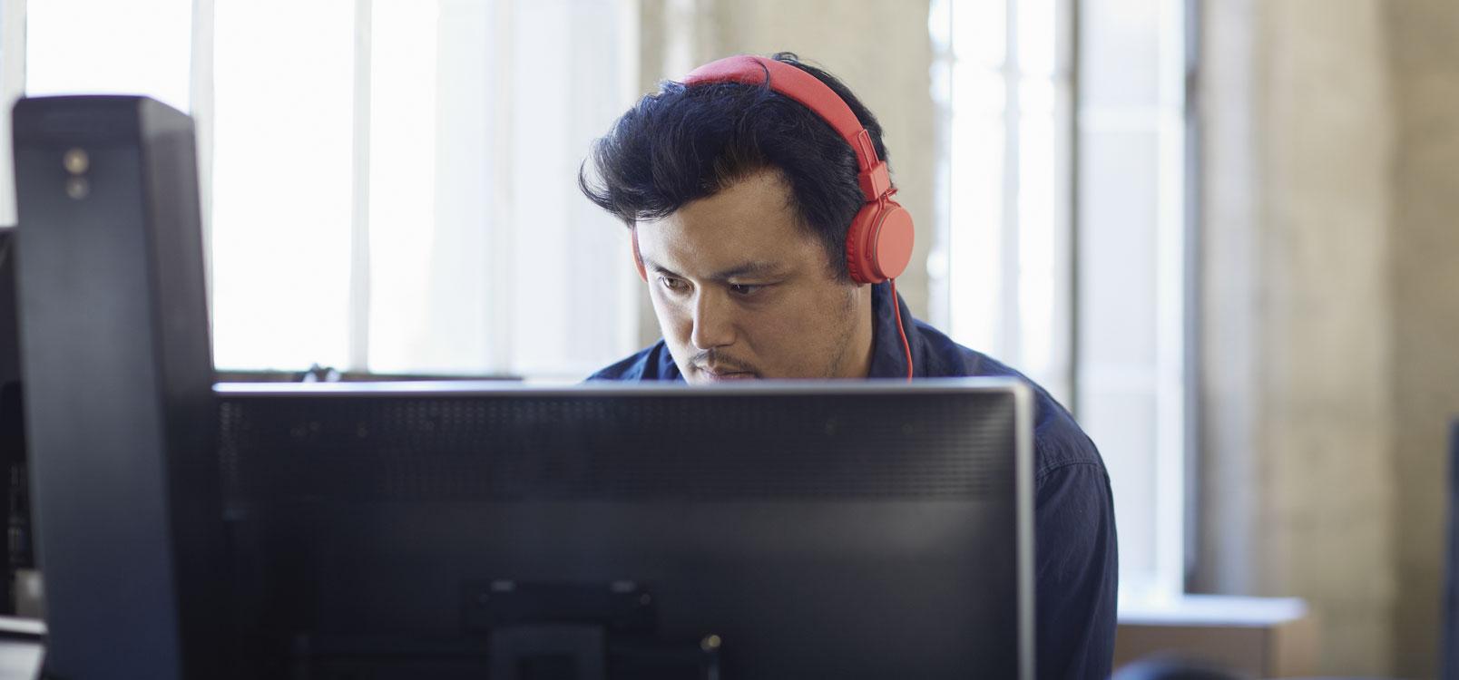 Seorang pria menggunakan headphone sedang bekerja dengan PC desktop menggunakan Office 365 untuk menyederhanakan TI.