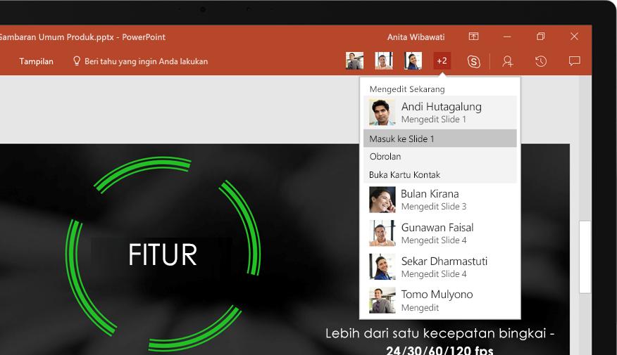 Laptop menampilkan slide presentasi PowerPoint yang sedang dikerjakan bersama oleh tim.