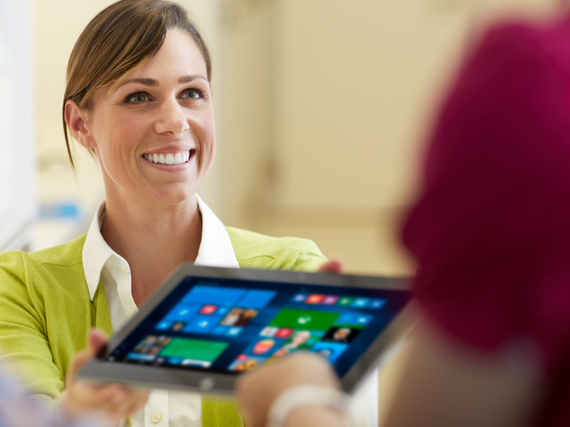 Woman handing laptop with Windows 10 to another person