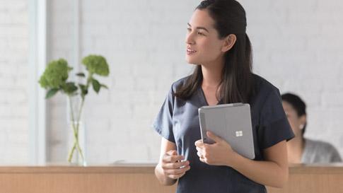 Un'infermiera cammina tenendo in una mano un dispositivo Surface Go in modalità Tablet