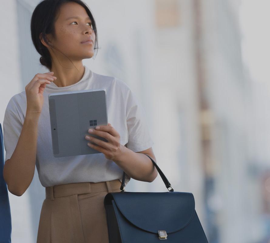 in una strada cittadina, una donna tiene con una mano il suo dispositivo Surface Go in modalità Tablet