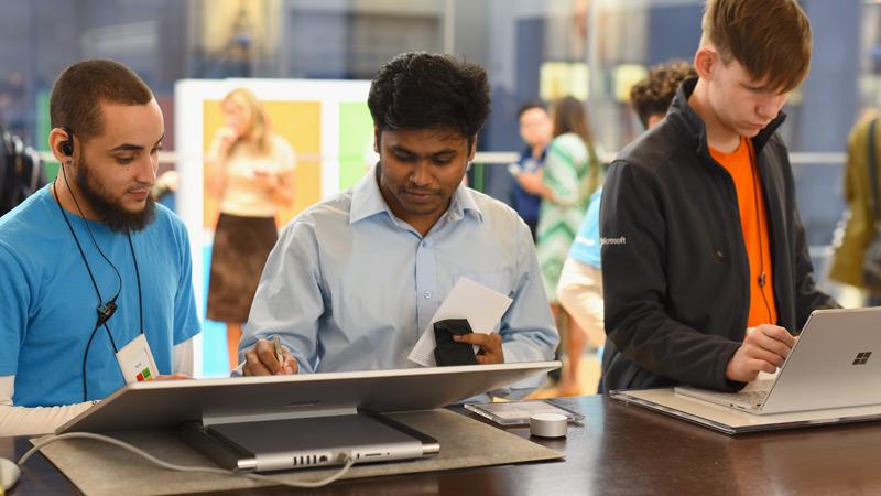 Alcuni clienti provano i dispositivi Surface Studio 2 e Surface Book 2 in un punto vendita Microsoft con l'aiuto di un esperto Microsoft per le PMI.