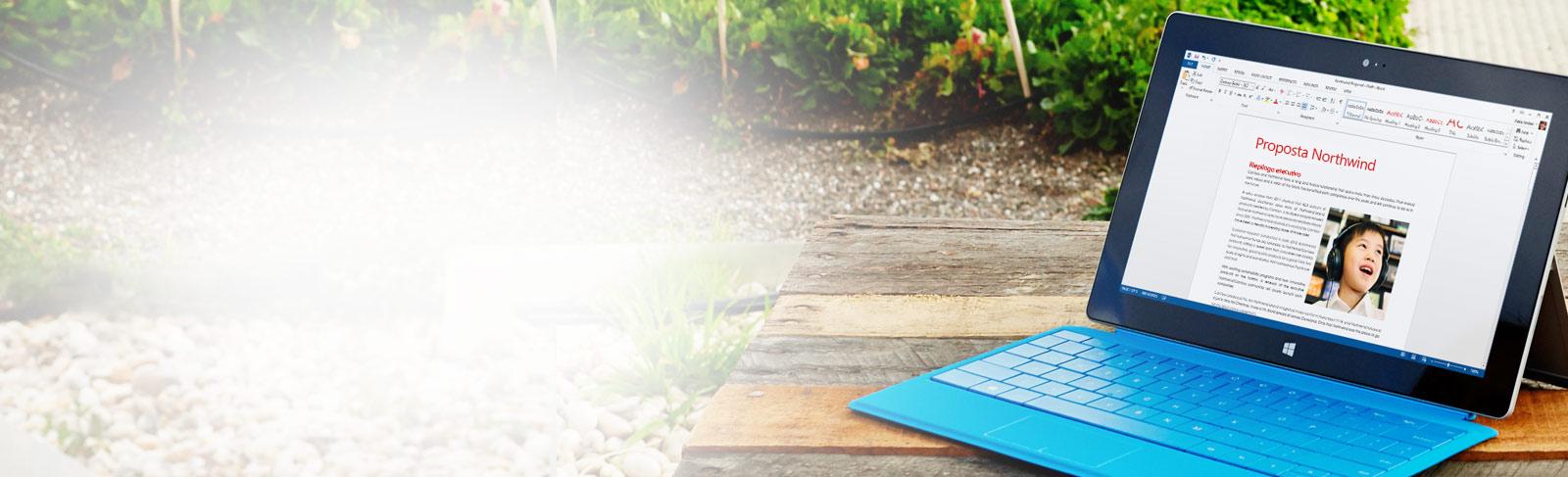 Persona al lavoro che digita su una tastiera, davanti a uno schermo che mostra un documento di Word.