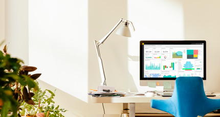 Scrivania con sedia blu e schermo del computer che visualizza PowerBI.