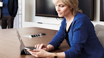 Persona in una sala riunioni che lavora con un laptop e guarda il suo telefono