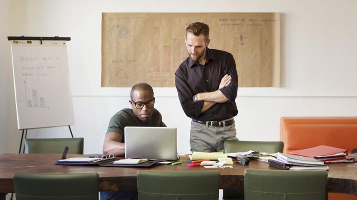 Vista frontale di due uomini al lavoro su un tavolo di una sala riunioni che guardano un portatile aperto.