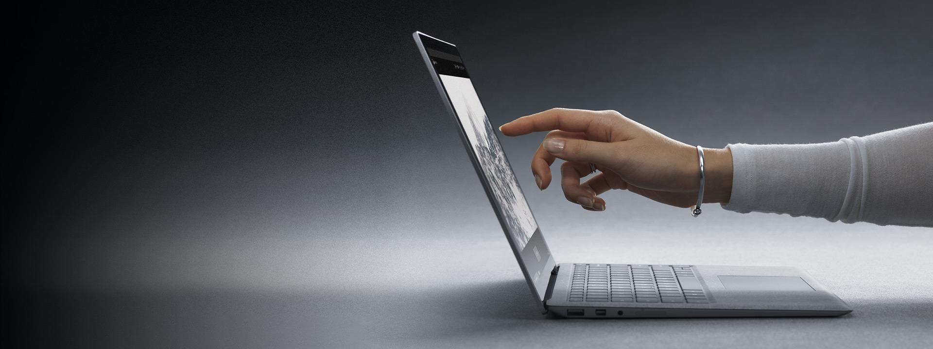 Una ragazza tocca lo schermo di un computer Surface Laptop 2