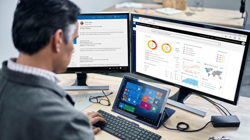 Un uomo osserva Windows Defender Center sugli gli schermi della sua postazione